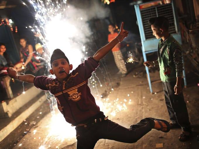 A boy leaps out of the way as firecrackers explode during a Nov. 13 Diwali festival in New Delhi, India. Diwali, the festival of lights, is dedicated to Lakshmi, the goddess of wealth.