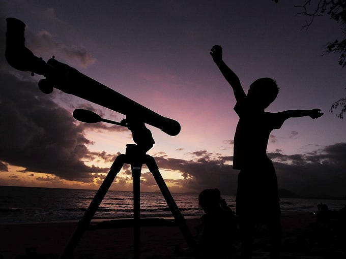 A boy gets ready to view the solar eclipse  with his telescope on Nov. 14 in Palm Cove, Australia. Thousands of people gathered in North Queensland to enjoy the solar eclipse, the first in Australia in a decade.