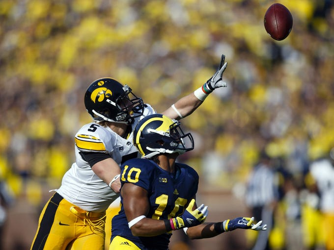 Michigan Wolverines wide receiver Jeremy Gallon (10) makes a reception as Iowa Hawkeyes defensive back Tanner Miller (5) defends in the second quarter at Michigan Stadium.