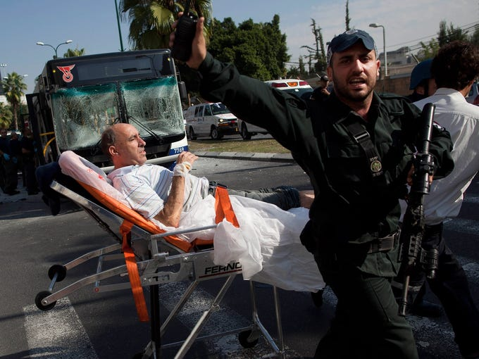 Israeli rescue workers and paramedics transport a wounded man from the site of a bus bombing Nov. 21 in Tel Aviv. Ten people were wounded when a bomb ripped through a commuter bus near the Defense Ministry building.