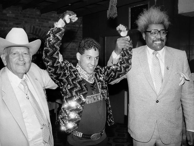 """In this Dec. 9, 1986 photo, Hector """"Macho"""" Camacho, the WBC lightweight boxing champion at the time, is escorted by Marty Cohen, left, and boxing promoter Don King, right, during a news conference in New York."""