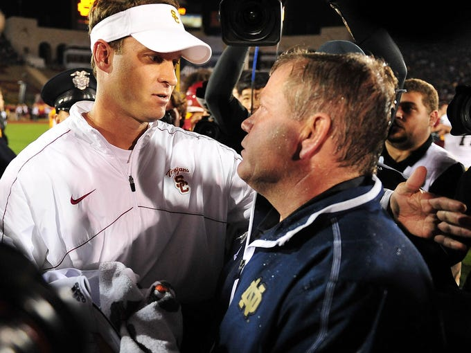 Southern California Trojans head coach Lane Kiffin meets with Notre Dame Fighting Irish head coach Brian Kelly following the 22-13 loss at the Los Angeles Memorial Coliseum.