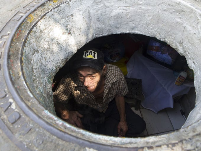 Miguel Restrepo looks out from the sewer where he lives with his wife, Maria Garcia, on Dec. 4 in Medellin, Colombia. The couple have lived for more than 20 years in the sewer.