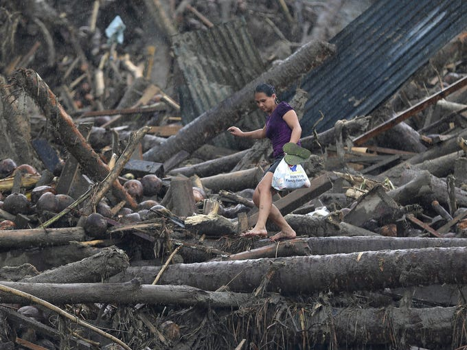 A woman carefully walks over storm debris as she carries a bag of relief supplies to her home on Dec. 7 in New Bataan township, Philippines. Rescuers were digging through mud and debris to retrieve bodies after Typhoon Bopha struck the southern Philippines on Dec. 4.