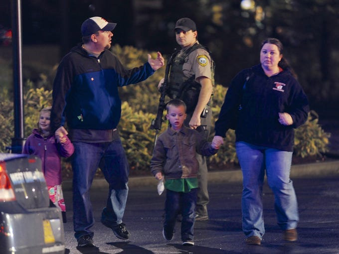 A family leaves the scene of a shooting at a suburban Portland, Ore., mall crowded with holiday shoppers. A gunman killed two people and wounded at least one other before taking his own life, sheriff's deputies said.