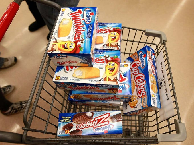 A customer heads to the checkout stand with a shopping cart loaded with Hostess Twinkies and Ding Dongs on Dec. 11 at a Jewel-Osco grocery store in Chicago. The chain purchased the last shipment of 20,000 boxes of Hostess products.