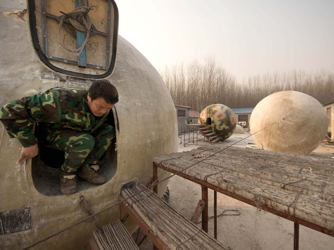 "Farmer Liu Qiyuan exits one of his seven survival pods on Dec. 11 at his home in Qiantun, China. Inspired by the apocalyptic Hollywood movie ""2012"" and the 2004 Indonesian tsunami, Liu hopes his creations will be adopted by governments and international organizations."