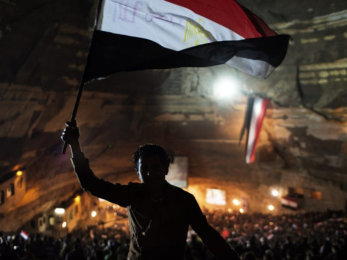 An Egyptian flag is waved as thousands of Egyptian Coptic Christian attend a Mass celebration in the Cave Cathedral or St Sama'ans in the Manshiet Nasser district of Cairo on December 13, 2012.