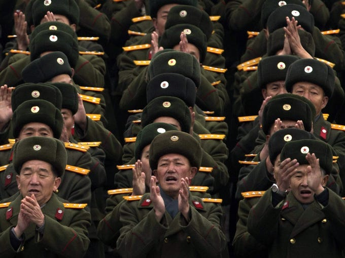 North Korean soldiers applaud during a mass rally Friday. It was organized to celebrate the success of a rocket launch that sent a satellite into space.