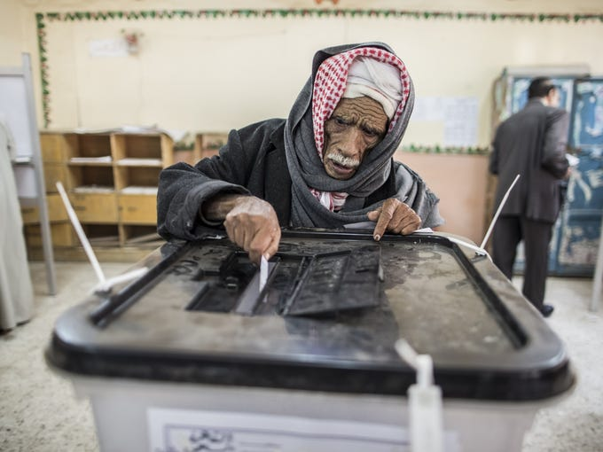 An Egyptian man casts his vote Saturday in a referendum on a disputed constitution drafted by Islamist supporters of President Mohammed Morsi in Cairo.