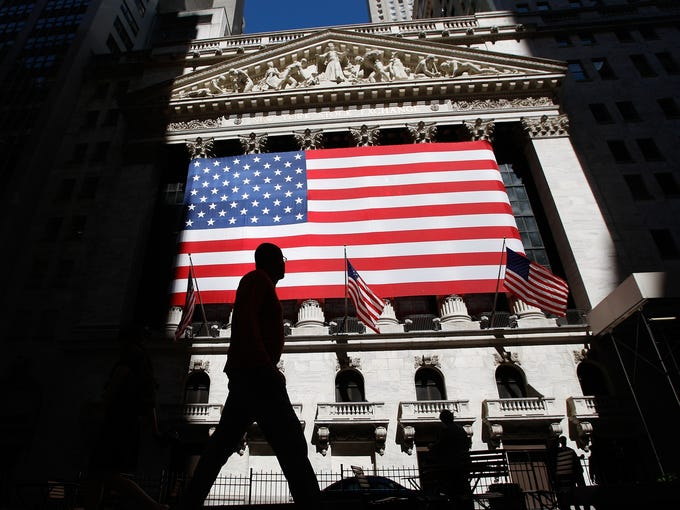 A person walks past the New York Stock Exchange on July 2, 2007. The New York Stock Exchange is being sold to a rival exchange for $8 billion, ending more than two centuries of independence. The buyer, IntercontinentalExchange Inc., is based in Atlanta. The deal still needs approval from regulators and shareholders.