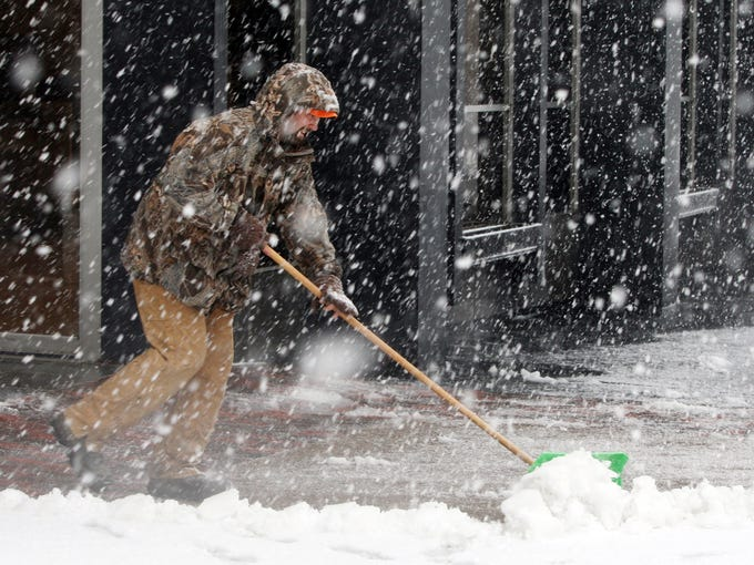 Brad Johnson pushes snow off the sidewalk as snow continues to fall in Burlington, Iowa.