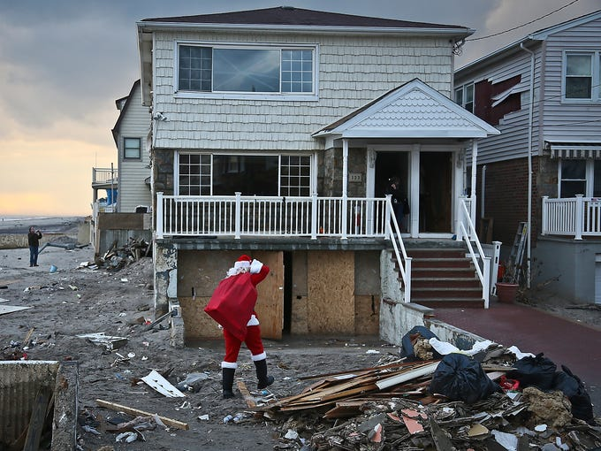 Michael Sciaraffo, dressed as Santa Claus, delivers a toy to a home damaged during Hurricane Sandy on Dec. 18 in Bell Harbor, N.Y. Using Facebook, Sciaraffo started a charity to collect and personally deliver toys to children affected by the storm.