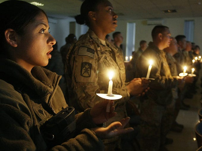 U.S. Army Spec. Gloria Camacho, left, and other members of the International Security Assistance Force celebrate Christmas eve at a base in Kabul, Afghanistan.