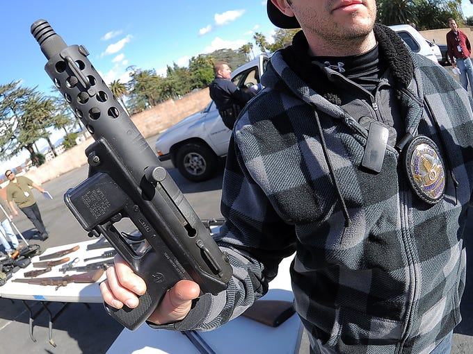 A Los Angeles police officer holds a weapon turned in during a gun buyback event on Dec. 26 in Van Nuys, Calif. People turned in 420 handguns, rifles, shotguns and  assault rifles during the no-questions-asked event where weapons could be exchanged for gift cards.