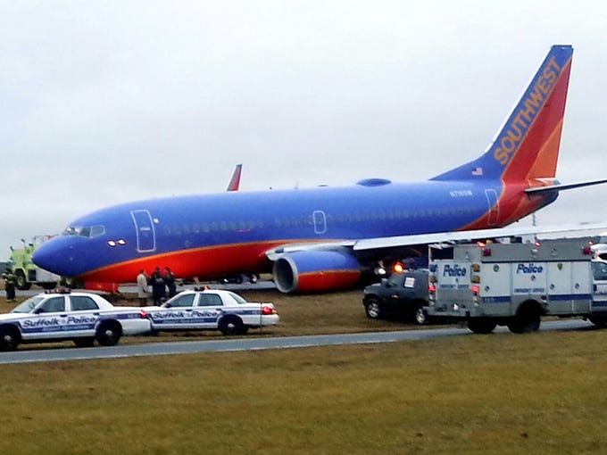 Rescue personnel respond to a Tampa-bound Southwest Airlines jet after it veered off the runway and got stuck in the mud at the Long Island McArthur Airport near  Ronkonoma, N.Y. on  Thursday, Dec. 27, 2012. Officials say there were no injuries to the 129 passengers and five crew members.