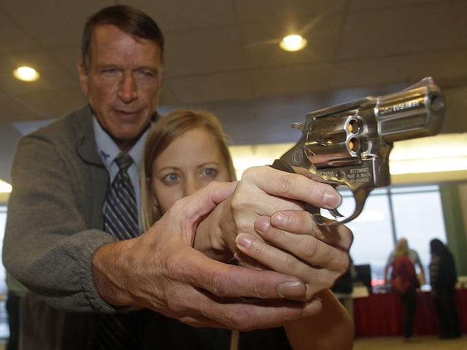 Personal defense instructor Jim McCarthy shows Cori Sorensen, a fourth-grade teacher from Highland Elementary School, how to hold a .357 magnum revolver during concealed weapons training for 200 teachers on Dec. 27 in West Valley City, Utah.