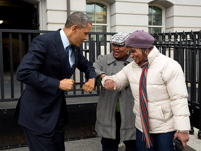 President Obama greets two General Services Administration workers as he walked on West Executive Avenue on Dec. 31, 2012, in Washington, D.C. He gave them an elbow-bump, because he had just applied a liquid sanitizer on his hands.