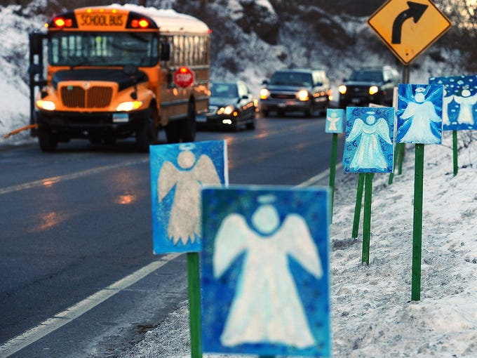 A bus carrying elementary school students from Newtown, Conn., stops in front of a memorial of 26 angels on Jan. 3 in Monroe. The Chalk Hill School in Monroe was overhauled for Sandy Hook students following a Dec. 14 shooting that killed 26 people.