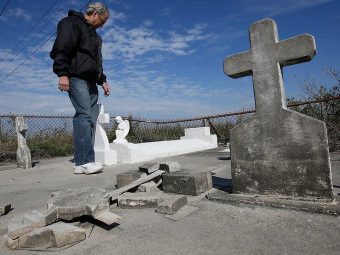 Windell Curole, general manager of the South Lafourche Levee District, walks through his small family cemetery on Dec. 29, 2012, near Leeville, La. Two dozen cemeteries across southeast Louisiana are rapidly sinking or washing away because of erosion and sinking accelerated by powerful storms such as hurricanes Katrina, Rita, Gustav, Ike, Lee and Isaac. Local residents say 11 cemeteries in Jefferson Parish have repeatedly flooded since Hurricane Katrina. In Lafourche, Terrebonne and Plaquemines parishes, more than a dozen others have succumbed to tidal surge. Some have more than 300 gravesites.