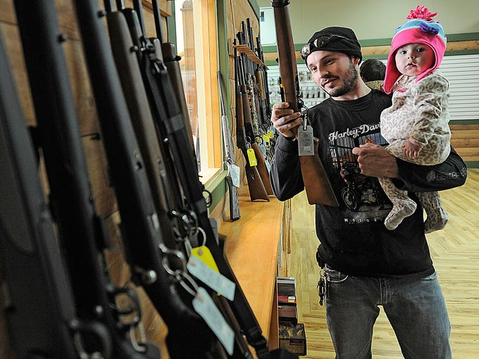 Tyler Hook looks at a rifle while holding his daughter, Emma, at Highsmith Guns on Jan. 2 in Greenfield, Ind. Highsmith Guns is seeing a rush on semiautomatic rifles. The AR-15 and AK-47 are the most popular.