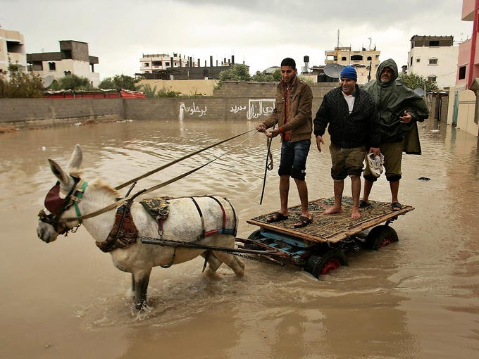 Palestinian men use a donkey cart to cross a flooded area on Jan. 9 in Rafah, Gaza Strip. Violent storms caused serious flooding and cut electricity to thousands of homes.