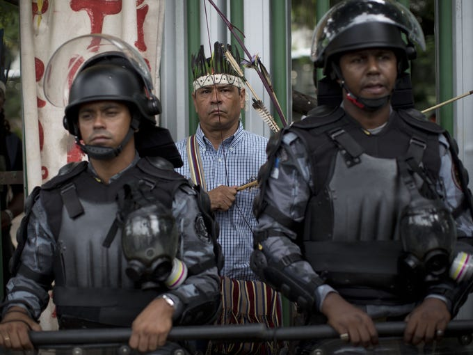 A man wearing a headdress and holding a bow and arrow stands behind two police in riot gear Jan. 12. Police surrounded a settlement of indigenous people next to Rio de Janeiro's Maracana stadium, preparing to evict them as soon as a court order arrived.