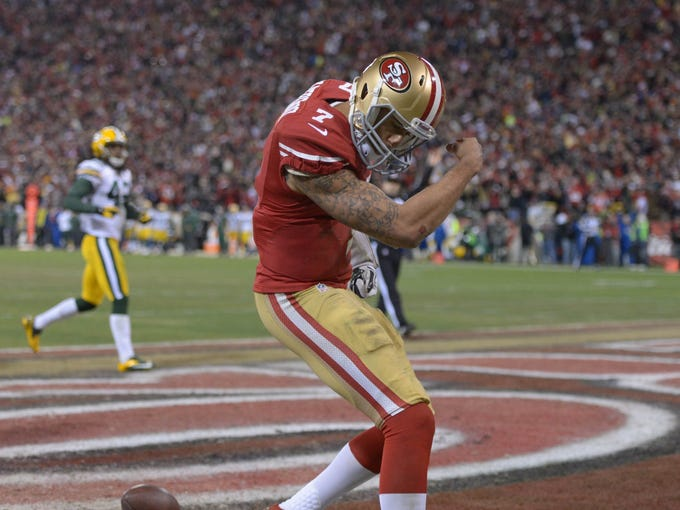 49ers quarterback Colin Kaepernick (7) celebrates after scoring a touchdown against the Packers during the third quarter of the NFC divisional playoff game at Candlestick Park.