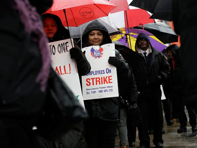 Striking bus drivers and their supporters walk a picket line in front of a bus depot on Jan. 16 in New York City. Eight thousand school bus drivers are striking over job protection, leaving 152,000 public school students and their parents to find another way to get to school.