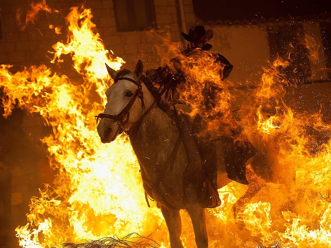 A rider jumps his horse over a bonfire on Jan. 16 in San Bartolome de Pinares, Spain. People are honoring St. Anthony, the patron saint of animals, by riding horses over bonfires to purify and protect them during the traditional Luminarias festival that has been held in this village for 500 years.