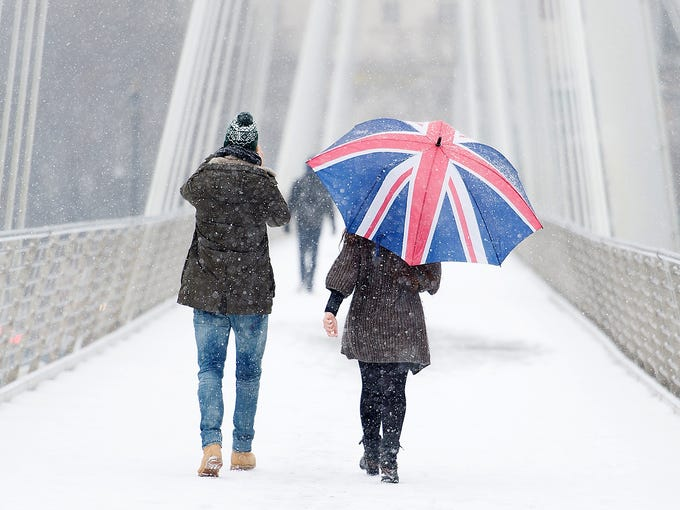 People cross the Jubilee Bridge as snow falls on Jan. 18 in central London. Heavy snow swept across Britain, forcing airports to cancel flights and 2,000 schools to close.
