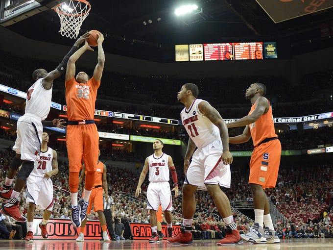 Syracuse Orange forward DaJuan Coleman (32) shoots against Louisville Cardinals center Gorgui Dieng (10) during the first half at the KFC Yum! Center.
