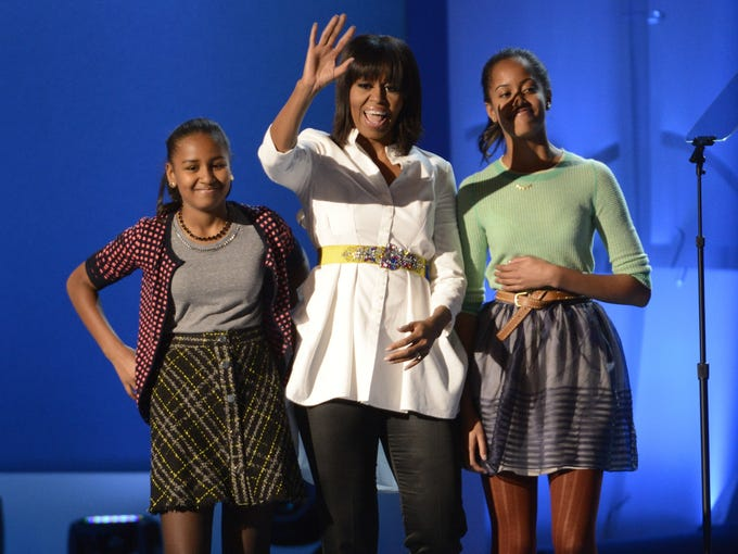 Michelle Obama, center, and daughters Sasha, left, and Malia, greet the crowd at the Kids' Inaugural: Our Children. Our Future event in Washington Jan. 19. The festivities were part of the 57th Inauguration weekend of events.