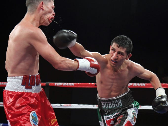 In the first title fight Saturday night on HBO at Madison Square Garden, Rocky Martinez, left, grimaces after being touched by challenger Juan Carlos Burgos.