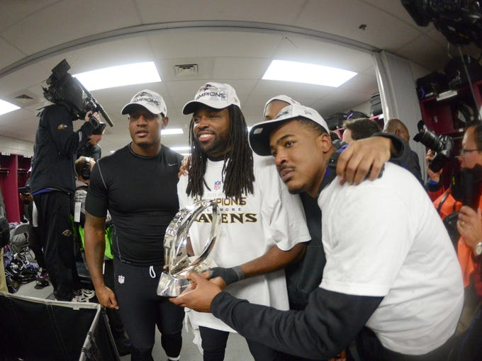Baltimore Ravens wide receiver Torrey Smith (center) and tight end Ed Dickson (left) and running back Anthony Allen (right) pose with the Lamar Hunt Trophy after defeating the New England Patriots 28-13 in the AFC championship game at Gillette Stadium.