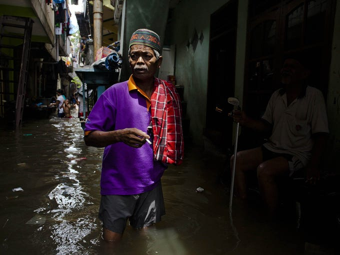 A man makes his way through floodwaters in North Jakarta, Indonesia, on Jan. 20, 2013. The death toll has risen to at least 21 since severe flooding struck the city on Jan. 17.
