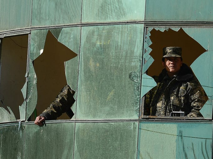 Security troops look through a broken window after a battle with Taliban insurgents on Jan. 21 in Kabul, Afghanistan. Three police officers were killed when a Taliban suicide squad stormed the Kabul police headquarters at dawn. NATO troops joined Afghan forces during a battle that lasted for more than eight hours.