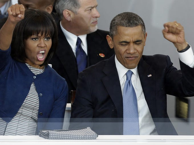 Fist pump! President Obama and first lady Michelle Obama cheer as bands march past the president's reviewing stand near the White House on Monday.