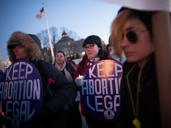 Attendees listen during a candlelight vigil organized by the National Organization for Women in front of the U.S. Supreme Court on Tuesday in Washington.