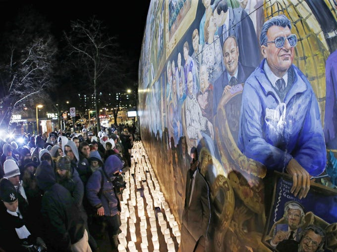 Candles surround a mural containing a likeness of former Penn State football coach Joe Paterno, at a candlelight memorial on the first anniversary of his death in State College, Pa.