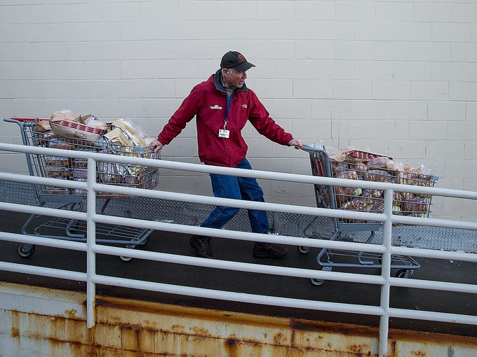 Dan Nidey, a volunteer with the food rescue organization Table to Table, wheels two carts filled with donated baked goods from the First Avenue Hy-Vee store on Jan. 9 in Iowa City, Iowa.  A report from The Gazette in Cedar Rapids shows 12% of the meals prepared by University of Iowa Hospitals and Clinics were sent to a landfill despite the university's goal to divert 60% of food waste by 2020.