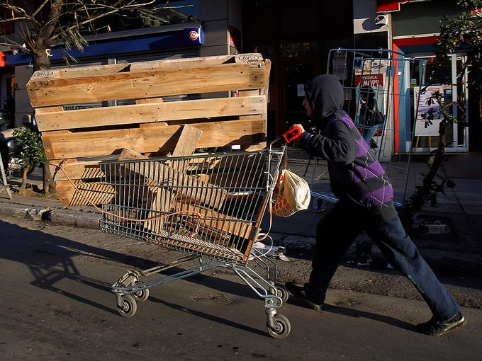 A boy carts away wooden palettes scavenged from recycling bins to use as firewood on Jan. 15 in Thessaloniki, Greece. A steep increase in heating costs has forced many people to switch from heating oil to wood-burning stoves or fireplaces for warmth. But Illegal loggers are slashing through forests devastated by years of summer wildfires, and air pollution from wood smoke is choking the country's main cities.