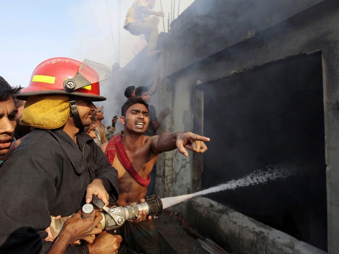 Bangladeshi firefighters and volunteers work to douse a fire Saturday at a two-story garment factory in Dhaka, Bangladesh. The fire swept through the factory killing at least six women and injuring five more, police and fire officials said.