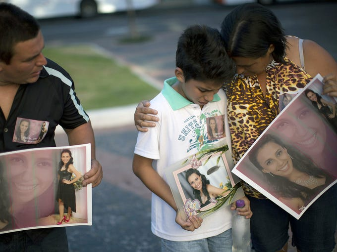 Relatives hold photographs of Pamella Lopes, who died in a fire at the Kiss nightclub in Santa Maria, Brazil, on Jan. 28.
