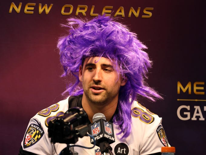 Baltimore Ravens tight end Dennis Pitta wears a purple wig as he is interviewed during media day in preparation for Super Bowl XLVII against the San Francisco 49ers at the Mercedes-Benz Superdome.