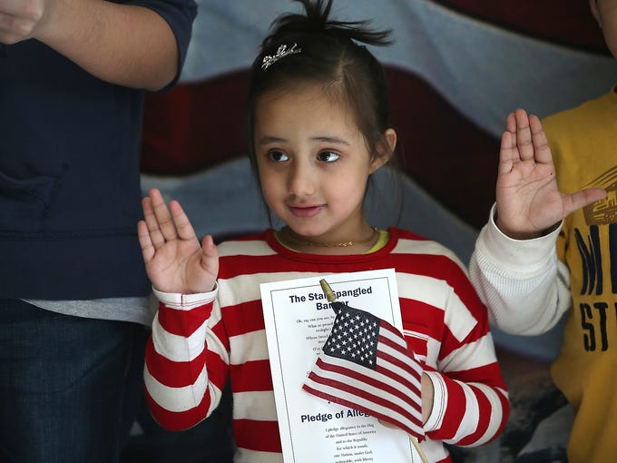 Malaika Chaudhary, whose parents immigrated to the USA from Pakistan, participates in a citizenship ceremony at the U.S. Citizenship and Immigration Services district office on Jan. 29 in New York City. In 2012, 118,000 immigrants applied for U.S. citizenship and 2,500 children received citizenship certificates in New York City.
