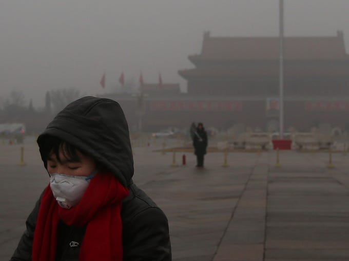 A Chinese tourist wears a mask at Tiananmen Square on Jan. 31 as severe pollution blankets Beijing. Five days of heavy smog that choked the capital weakened slightly after a light rainfall.