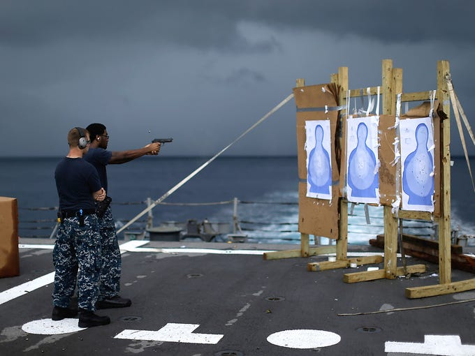 U.S. Navy sailors practice with pistols on the flight deck of the USS Underwood during a patrol on Oct. 11 in international waters near Panama. U.S. Army troops, Air Force pilots and Navy ships outfitted with Coast Guard counternarcotics teams are being deployed to chase, track and capture drug smugglers.