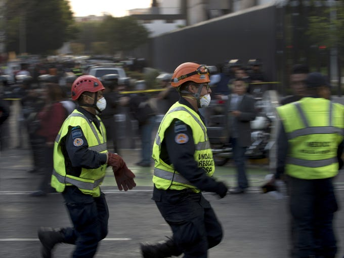 Rescue workers head for the skyscraper that houses the headquarters of Pemex in Mexico City.