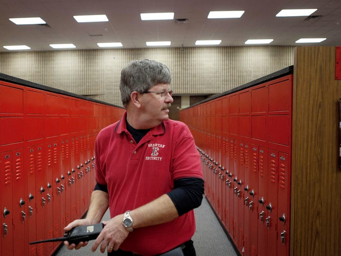 Emporia High School security guard Jeff Illk walks through a locker room while making his rounds at the school. The Emporia School District voted in January to allow the security guards at its schools to be armed with pistols starting Feb. 1.